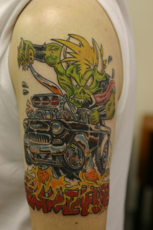 Superb Green Blue Black And Red Color Ink Car Tattoo On Arm For Boys
