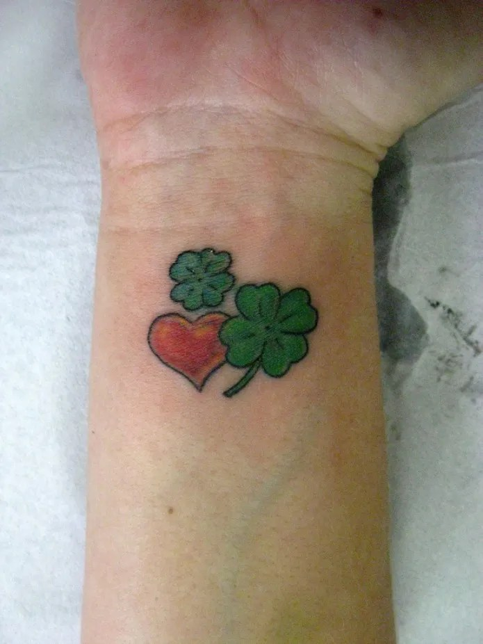 Terrific Red Black And Green Color Ink Heart & Clovers Tattoo On Wrist For Girls