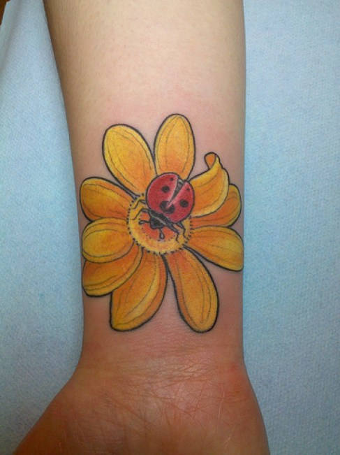 Traditional Yellow Black And Red Color Ink Wrist Lady Bug On Yellow Flower Tattoo On ARm For Girls