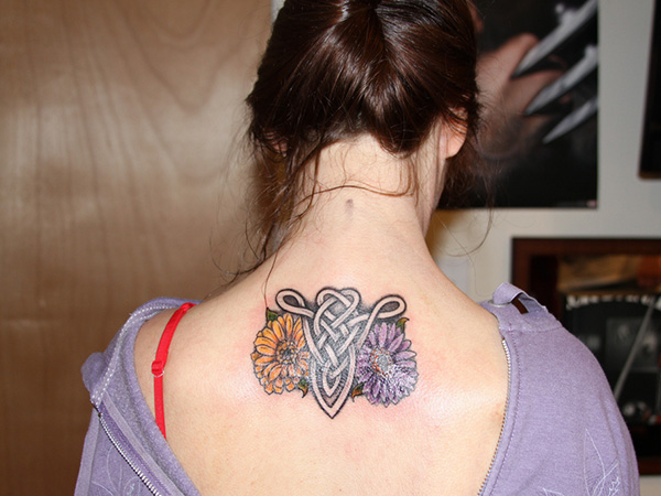 Weird Yellow Blue And Black Color Ink Celtic Aries Tattoo On Upper Back For Girls