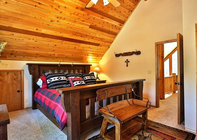 This bedroom has beautiful high wood ceilings and a comfy bed.