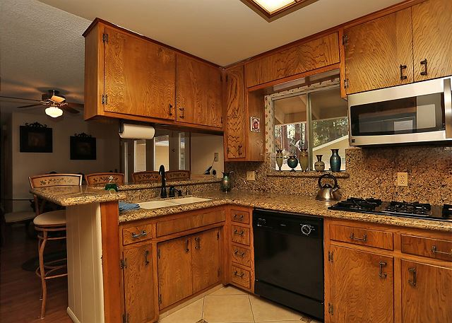 The wooden cabinetry and rustic decor give this kitchen a warm cabin feel.