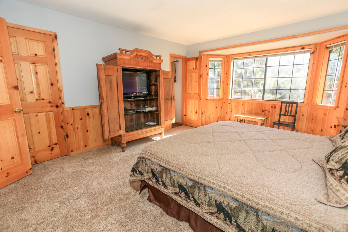 King sized bed in Master Bedroom with Entertainment center, internet access, and views of the forest.