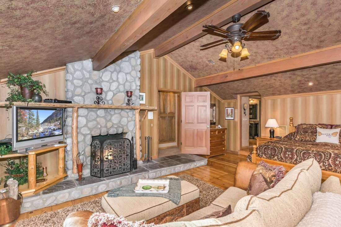 Large master bedroom has vaulted ceiling, fireplace, seating area and access to view decks