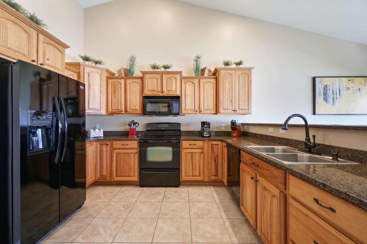 Electric Range with overhead microwave, dishwasher, and refrigerator with ice maker