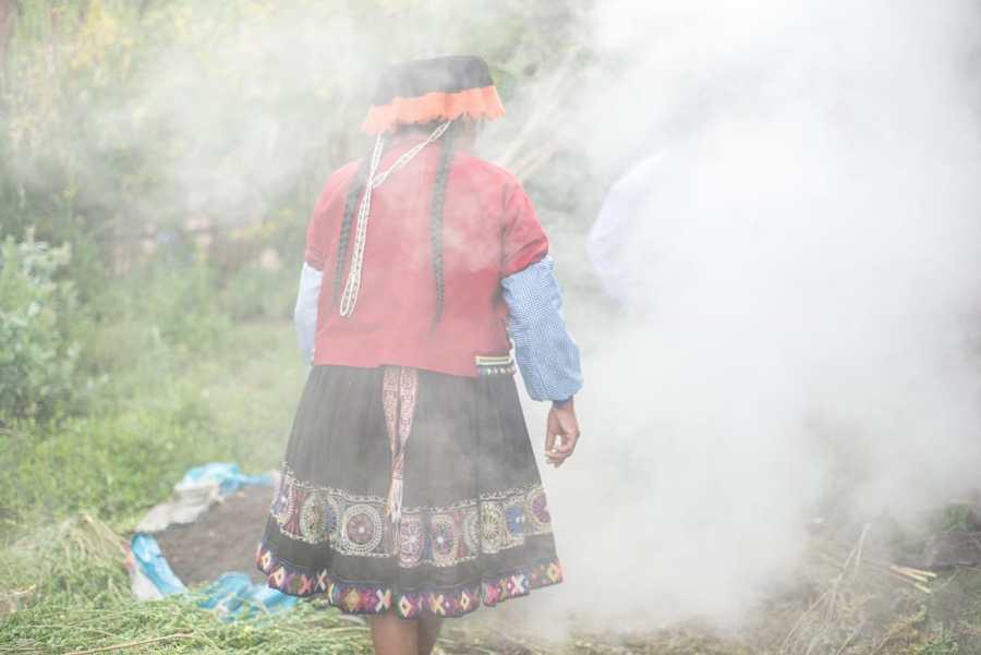 Pachamanca Dining Experience in Peru - Woman preparing the Pachamanca amidst Steam