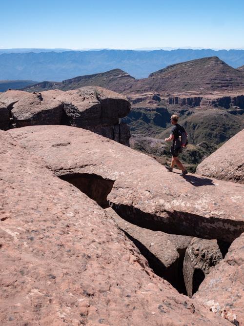 A man walks across a natural rock formation, Ciudad de Itas, Bolivia