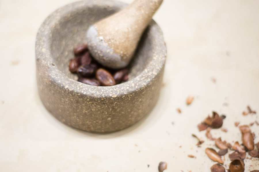 Cusco's chocolate museum - A mortar and pestle crushing cocoa nibs on a bench with cacao shells on the side