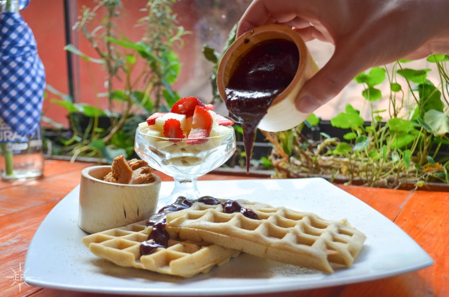Vegetarian food in Peru - Hand pouring chocolate sauce onto waffles.