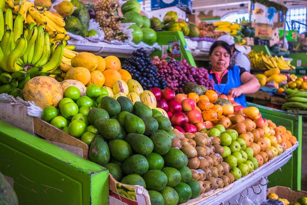 A woman sells fruits at a market in Ecuador.