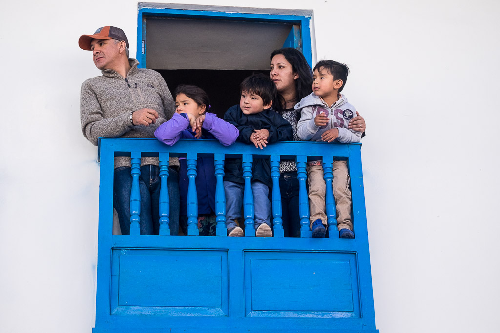 Spectators watch the festivities from a local balcony