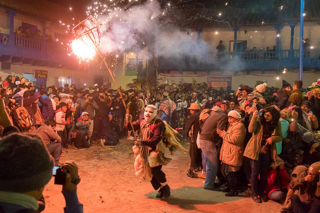 A masked character runs through the Virgin del Carmen Festival bearing fireworks