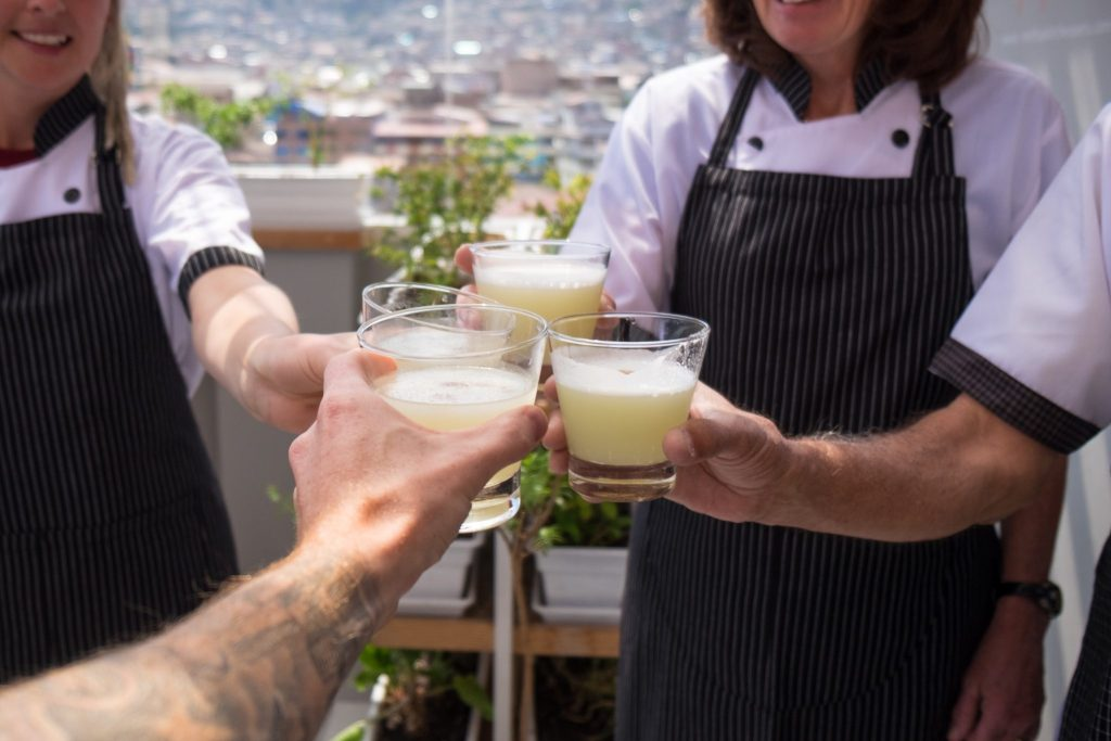 Cooking class in Cusco - Four hands making a toast with pisco.
