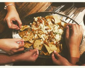 Piles of Nachoes with 4 hands reaching in for hte nacho love
