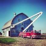 My dad painting the barn from in his fire truck boom