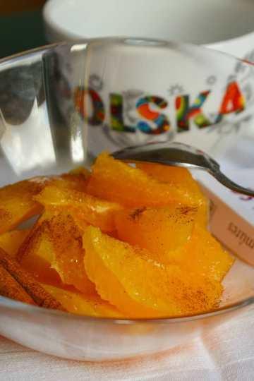 w szklanej salaterce, kawalki pomaranczy, posypane cynamonem, laska cynamonu, lyzeczka,