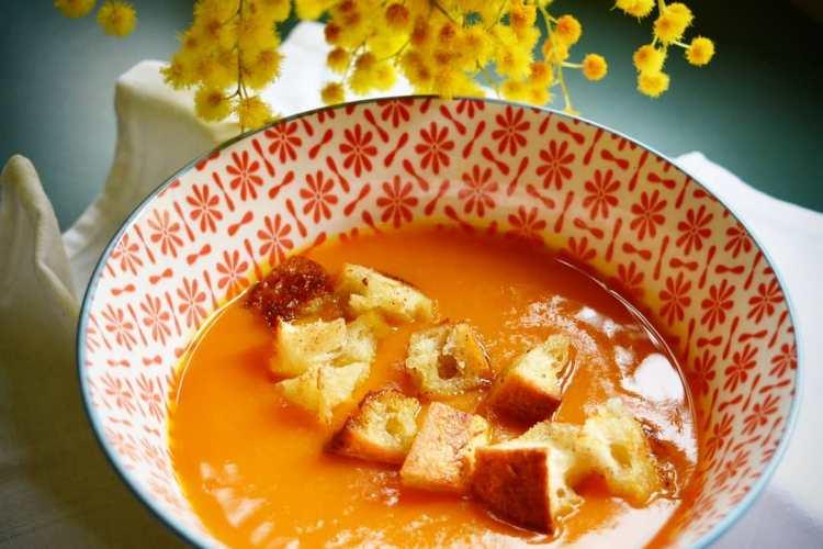 dans un bol soupe orange, croutons de pain, une branche de mimoza