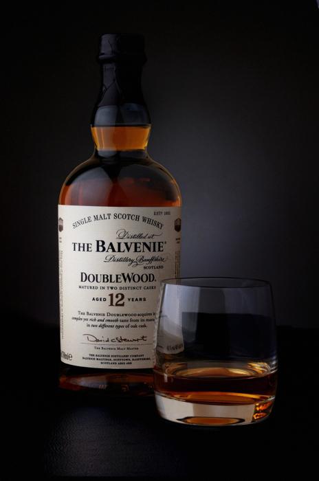 Photographie packshot d'une bouteille et d'un verre de whisky.