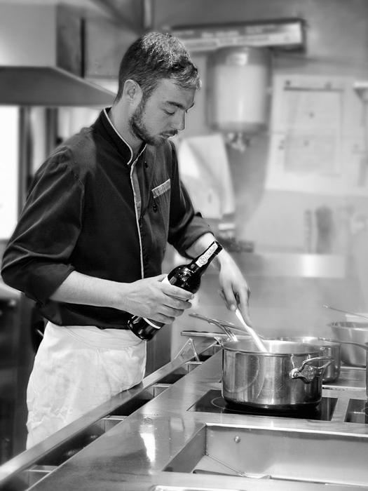 Photographie en entreprise de restauration d'un cuisinier au travail.