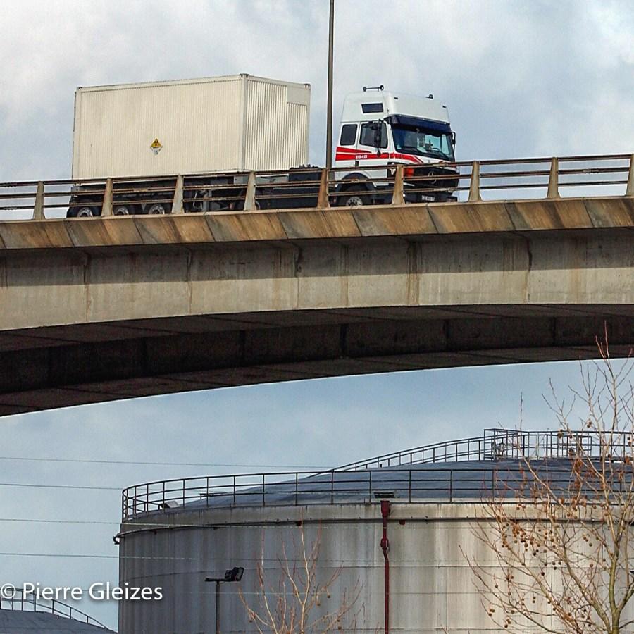 """2003, Caen. Note du photographe : Depuis que ma photo été publiée, ces convois n'empruntent plus ce viaduc.   """"LA COGEMA PRIS EN FLAGRANT DÉLIT DE MISE EN DANGER DE LA POPULATION FRANÇAISE POUR UN RACCOURCI DE 5 KM.  Un camion affrété par la Cogema transportant 150 kilos de plutonium de l'usine de la Hague à Marcoule photographié lors de son passage à Caen le 4  février 2003  Pour ne pas rallonger son parcours de 5 km (sur un voyage de 1100 km ) ce véhicule emprunte le périphérique nord de l' agglomération plutôt que le sud. Ce faisant, la cargaison est mise dans une situation non envisagée par les procédures de test exigées pour tenter d'assurer la sécurité de ce genre de transport.  Le type de container utilisé a été mis à l'épreuve pour une chute allant jusqu'à 9 mètres de hauteur. Le camion est ici entrain de franchir le viaduc de Cadix qui passe 30 mètres au dessus de l'Orne et des installations pétrolières du port de Caen.  La théorie de l'effet """"domino"""" explique l'origine de toutes les grandes catastrophes industrielles et humaines. Elle n'est pas prise en compte pour l'établissement de cet itinéraire qui met en proximité rapproché 150 kilos de plutonium avec des milliers de litres d'hydrocarbure.  Ces liquides dégageraient en cas d'incendie des températures pouvant aller bien au delà des seuils de résistance auxquelles ces containers ont été testés, soit 800° pendant une demi-heure."""