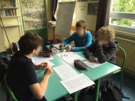 Trois élèves jouent à un jeu de rôle médiéval - fantastique avec des dés que je leur ai prêtés