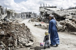 TOPSHOTS A Kurdish Syrian woman walks with her child past the ruins of the town of Kobane, also known as Ain al-Arab, on March 25, 2015. Islamic State (IS) fighters were driven out of Kobane on January 26 by Kurdish and allied forces. AFP PHOTO/YASIN AKGUL