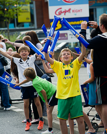 Children waving at the Media One bus waiting for the Olympic Torch relay in Cromer, North Norfolk