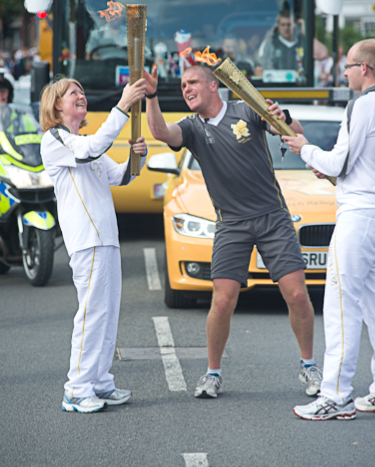 Nicky Wardale receiving the Flame from Harry Heathfield during the Olympic Torch relay in Cromer, North Norfolk