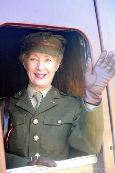 Female army officer waving goodbye from train