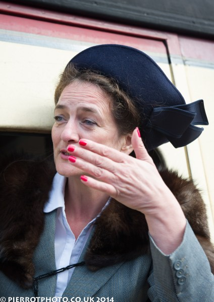 1940s weekend in Sheringham North Norfolk 2014 - attractive woman with blue hat kissing goodbye from train