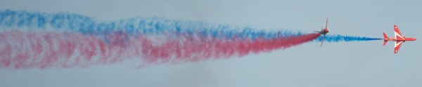Two Red Arrows flying with with red and blue vapour trails at Cromer carnival