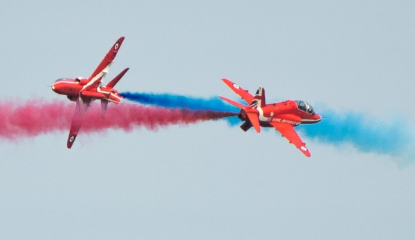 Two Red Arrows passing each other with red and blue smoke at Cromer carnival