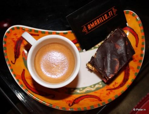 Pähkinäinen vaahtokarkki-suklaaleivos ja espresso lautasella.