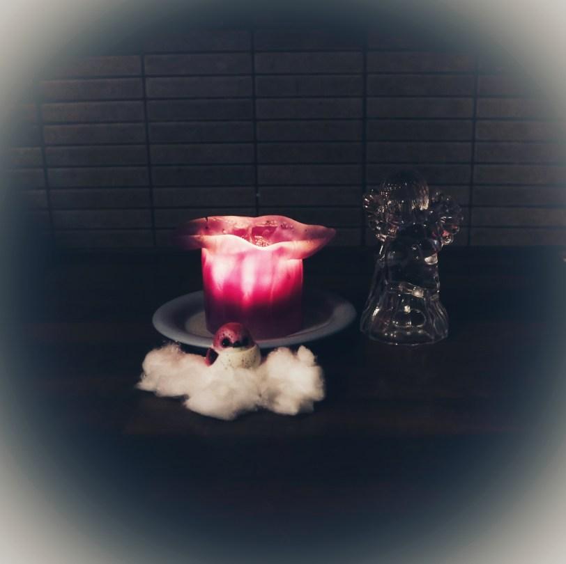 Pöydällä pyhäinpäivä kynttilä, enkeli ja lintu.