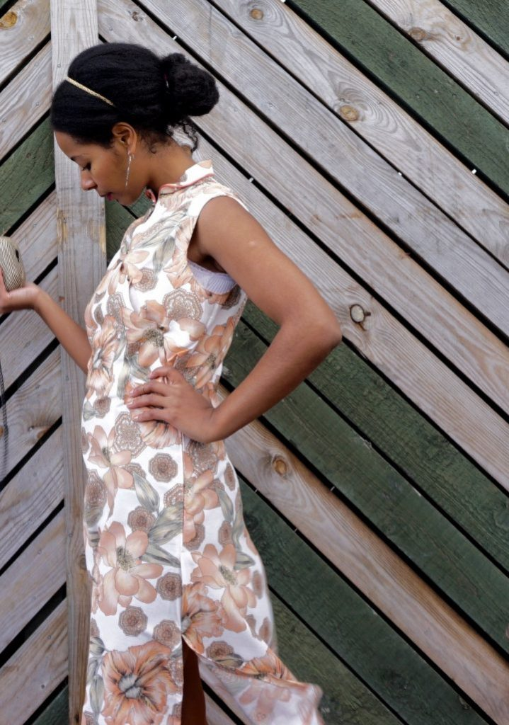 Megan is standing against a wooden fence. She is wearing her handmade qipao. The fabric has a floral print. Megan is standing sideways and she is looking down at the ground.