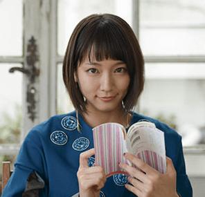 吉岡里帆が青い服を着て本を開いて見ている画像