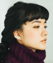 小島藤子が紫のセーターを着て少し顔(アゴ)を上げて斜め下を見ている画像