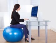 27863701 - side view portrait of businesswoman using computer while sitting on pilates ball in office