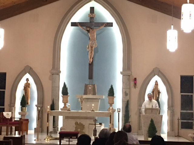 Deacon Tom Fox speaks at the ambo while the Blessed Sacrament is exposed on the altar at St. Monica parish in Converse