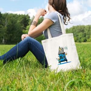 sac tote bag en coton blanc, pratique et ecologique, illustré avec la célèbre maison bleu sur pilotis en bord de mer réalisée par Abi notre artiste