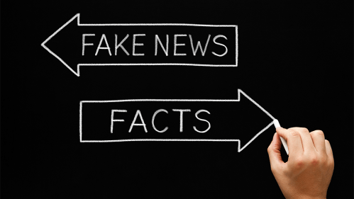 person's hand draws arrows pointing different directions representing fake news and facts