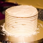 The cake after using a decorating scraper to create grooves in the cake.