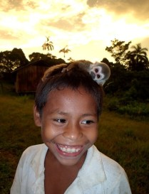 Smiling boy with monkey on the head
