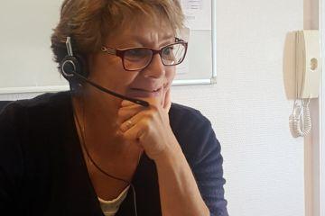 Patricia, ancienne médiatrice sociale devant son ordinateur de travail, un casque sur les oreilles