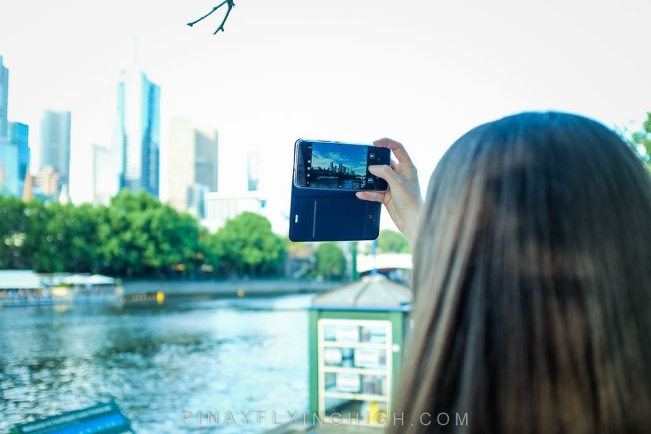 Girl taking a photo of Melbourne skyline.