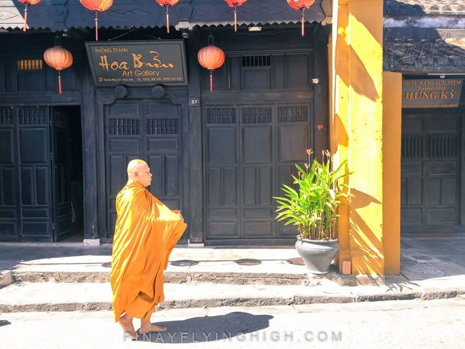 a monk walking in hoi an in the morning