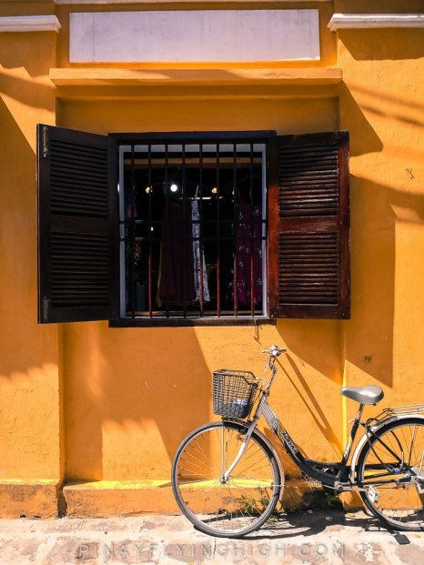 a bicycle under a window in hoi an