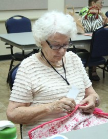 Paula Hassler sews a border into the quilt she is completing during a Thursday meeting of the group. (Photo by Hannah Dickens)