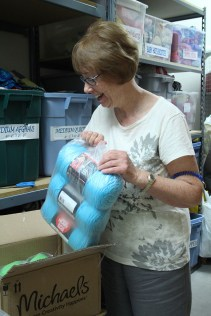 Supervisor Christy Summers opens up one of the boxes of brand new yarn for the group to use. (Photo by Hannah Dickens)