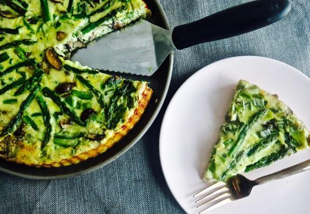 Sliced veggie quiche on white plate